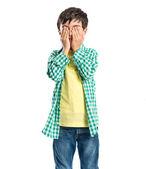 Boy covering his eyes over white background  — ストック写真