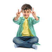 Boy making a victory sign on wooden chair over white background  — Foto Stock