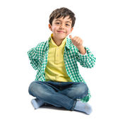 Boy making a OK sign on wooden chair over white background  — Foto de Stock