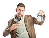Young businessman holding an antique clock over white background — Stock Photo