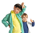 Kids making good and bad sign over white background  — Fotografia Stock