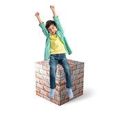 Lucky brunette kid sit on massive brick element  — Stock Photo