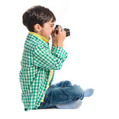 Boy photographing something over white background  — Stok fotoğraf