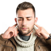 Handsome man covering his ears over white background  — Stock Photo