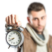 Young man holding an antique clock over white background  — Foto de Stock