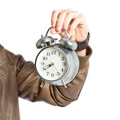 Young man holding an antique clock over white background  — Stockfoto
