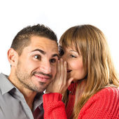 Young girl whispering to her boyfriend over white background  — Stock Photo