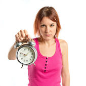Serious redhead girl holding a clock over white background — Stok fotoğraf