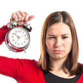 Surprised young woman holding an antique clock over white background — 图库照片
