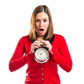 Surprised young woman holding an antique clock over white background — Stock Photo