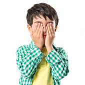 Boy covering his eyes over white background — Stock Photo