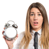 Young businesswoman holding an antique clock over white background  — 图库照片