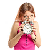 Serious redhead girl holding a clock over white background  — Stock Photo