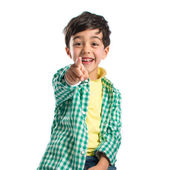 Boy pointing to the front on wooden chair over white background  — Stock Photo