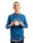 Redhead man holding an antique clock over white background  — Stock Photo