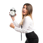 Young businesswoman holding an antique clock over white backgrou — Stock Photo