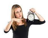 Happy blondr girl holding a clock over white background  — Stock Photo