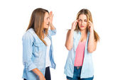 Girl shouting at her friend over white background  — Stock Photo