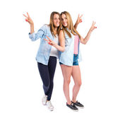 Friends doing victory gesture over white background  — Stock Photo
