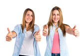 Friends with thumbs up over white background  — Stock Photo