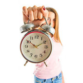Serious girl holding a clock over white background  — Stock Photo