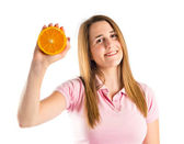 Young girl holding an orange over white background — Stock Photo