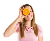 Young girl playing with orange over white background — Stock Photo