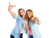 Friends making horn gesture over white background — Stock Photo