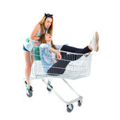 Girl inside supermarket cart over white background — Stock Photo