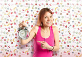 Happy redhead girl holding a clock over cute background — Stock Photo