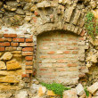 Ancient stone-brick wall with old window — Stock Photo
