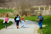 Two boys and two girls going to school — Stock Photo