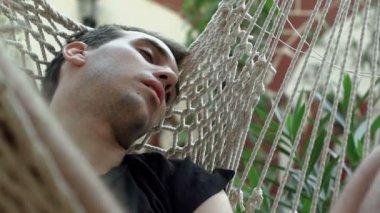 Drunk man sleeping in hammock outdoors — Stock Video