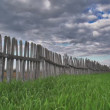 Stock Video: Epic time lapse of storm clouds over green meadow and wooden fence