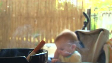 Smoke, cigarette, an ashtray and a baby . selective focus. — Stock Video