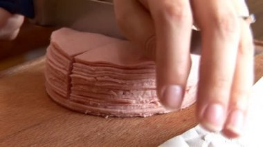 Cutting baloney on a wooden cutting board — Stock Video