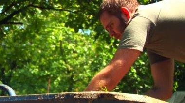 Young man digging in his backyard. — Stock Video