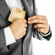 A businessman in a  suit putting money in his pocket — Stock Photo