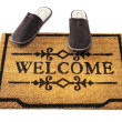 Welcome mat and slippers — Stock Photo