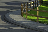 Timber fence and road — Stock Photo