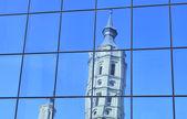 Reflection of Church de San Juan de los Panetes at modern glass — Stock Photo