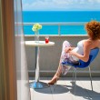 Young redhaired woman enjoying a sea view — Stock Photo