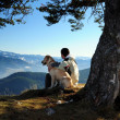 Man enjoying mountain view with his dog - Stock Photo