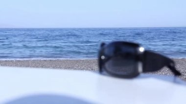 Sunglasses on beach table with sand and waves on background — Stock Video