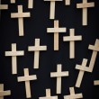 25 wooden crosses suspended on a black canvas — Stock Photo