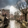 Murky canal meandering through medieval Bruges — Stock Photo