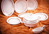 Dinnerware set on orange background — 图库照片