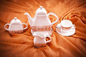 Dinnerware set on orange background — Zdjęcie stockowe
