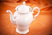 Teapot isolated on orange fabric background — Stok fotoğraf