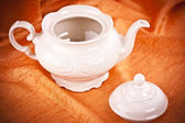 Teapot isolated on orange fabric background — Photo
